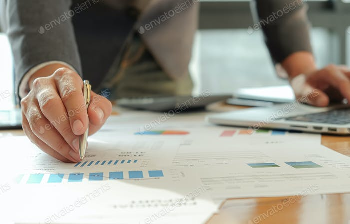 Businessmen use pen, laptop and mobile phone are planning a marketing plan to improve work quality.