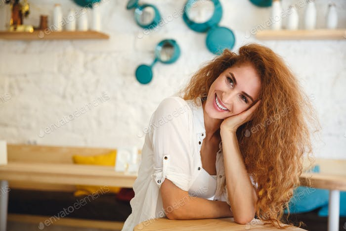 Pretty redhead young lady sitting in cafe while posing.
