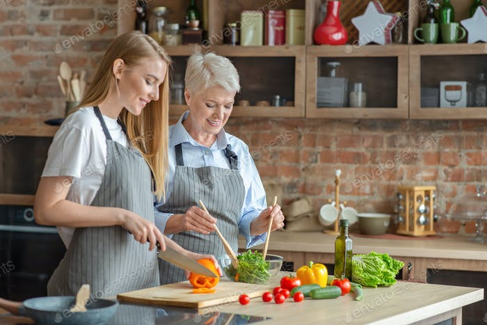 Young woman cooking healthy veggies salad with aged mom