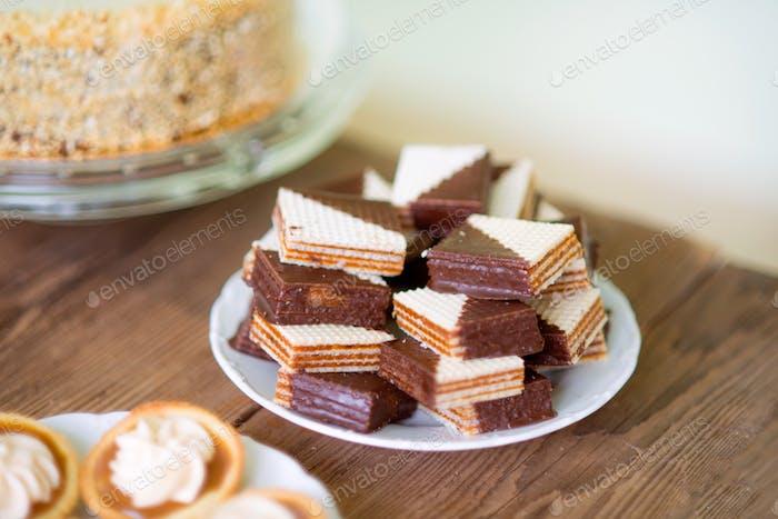 Nahaufnahme, Schokoladenwaffeln und Torten mit Marmelade und Sahne auf Plat