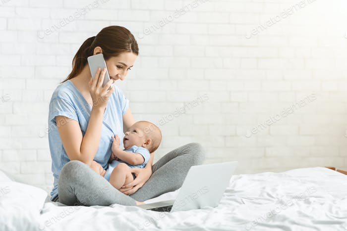 Young mother talking on mobile phone and nursing newborn child
