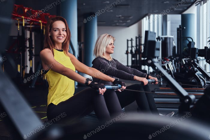 Two beautiful young women doing rowing practice in the gym