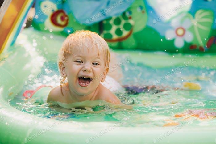 Kind spielt im Pool. Kleines Mädchen im Pool, lächelnd Kind