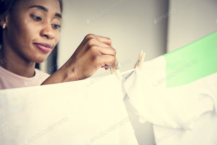 Closehup of black woman hanging washed clothes housework