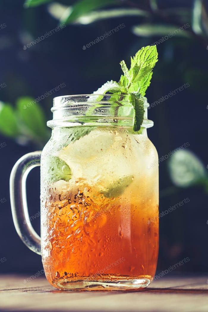 Ice black tea in a glass jar with fresh mint on a wooden table.