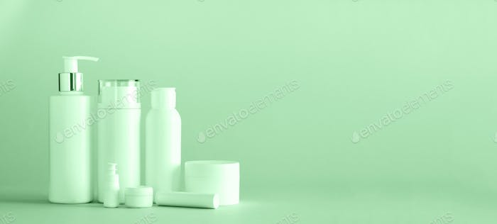 White cosmetic tubes on trendy mint color background with copy space. Skin care, body treatment