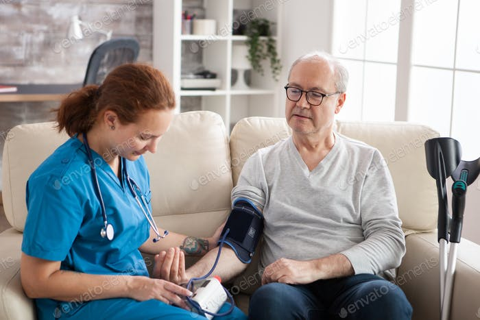 Female doctor reading blood pressure of old man