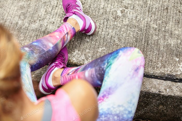 Top view of blonde female athlete in stylish leggings and purple sneakers sitting on sidewalk while