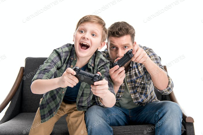 Father and son sitting on sofa and playing with joysticks isolated on white