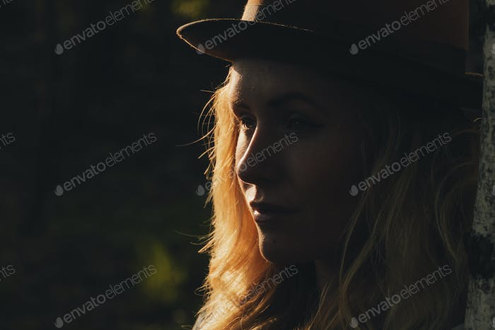 Portrait of a bohemian woman wearing a hat standig in a spring forest