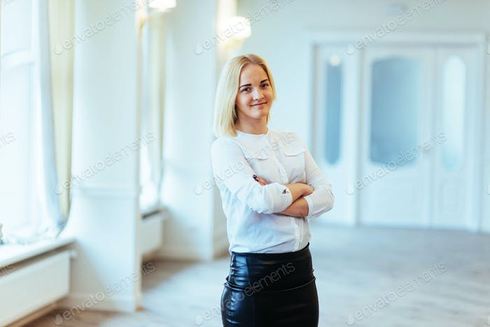 Happy business woman looking confident with modern building as b