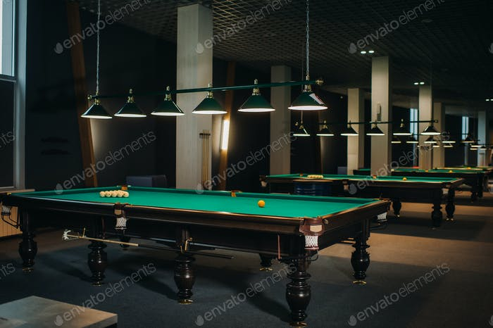 there are a lot of billiard tables with green surfaces and balls in the billiard club