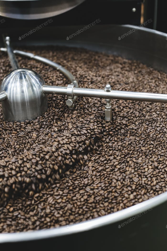 Freshly roasted aromatic coffee beans in a modern coffee roasting machine