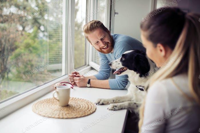 Schönes Paar entspannen zu Hause und lieben ihren Hund
