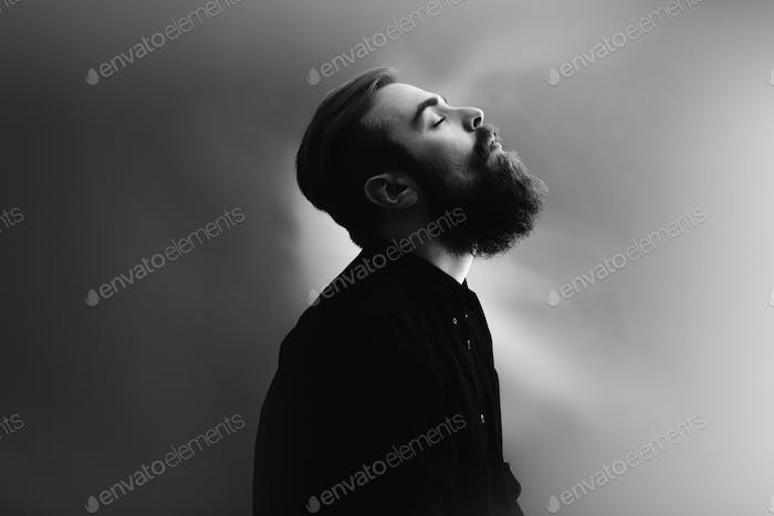 Black and white photo portrait of a stylish man in profile with a beard dressed in the black shirt