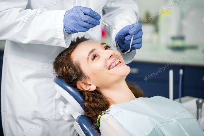 cropped view of dentist in latex gloves examining cheerful woman in braces
