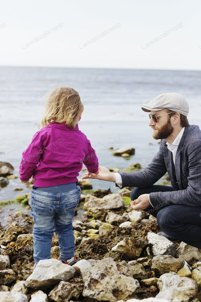 Father giving pebbles to daughter at beach