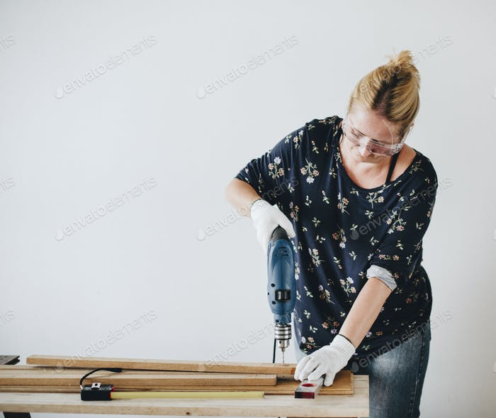 Woman drilling into a wooden plank