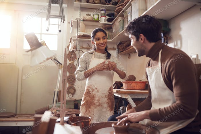 Couple Running Bespoke Pottery Business Working In Ceramics Studio Together