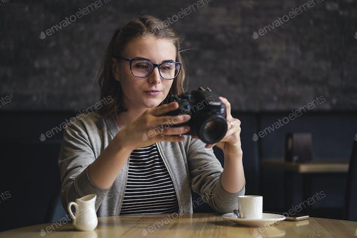 Junge weibliche Fotografin überprüfen ein Bild