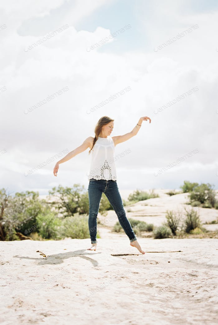 Barefoot woman wearing jeans, striking a pose in open space, her arms raised.