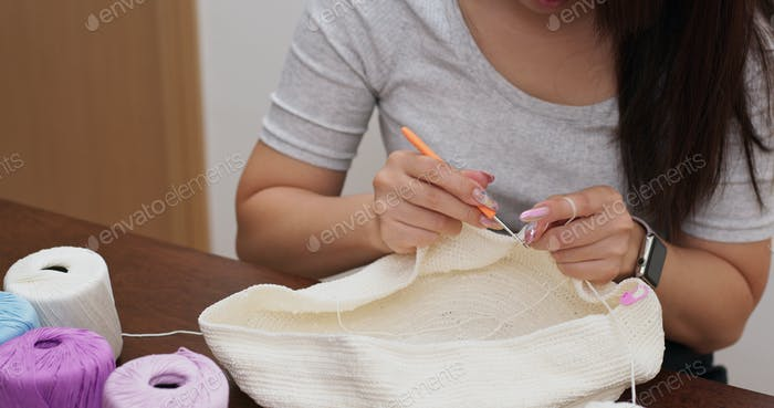 Woman hands knitting with crochet hook at home