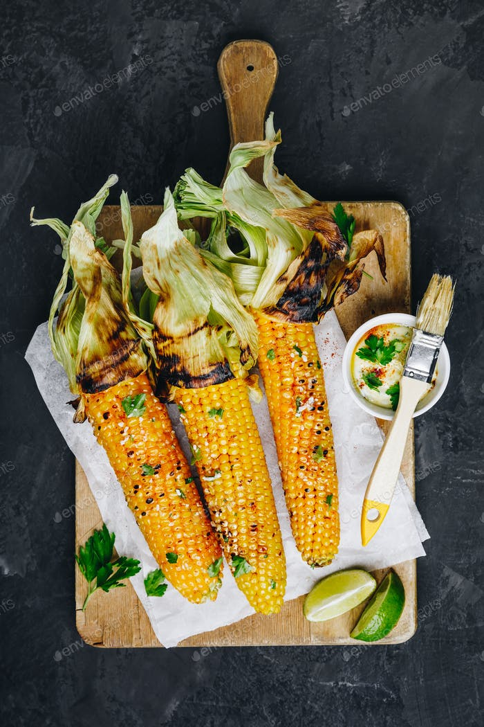 Roasted or grilled sweet corn cobs with garlic butter and lime.