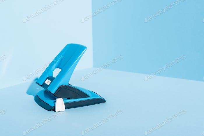 Blue Plastic Hole Puncher on Blue Background