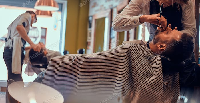 Thendy hairdresser at modern barbershop is working on client's haircut.