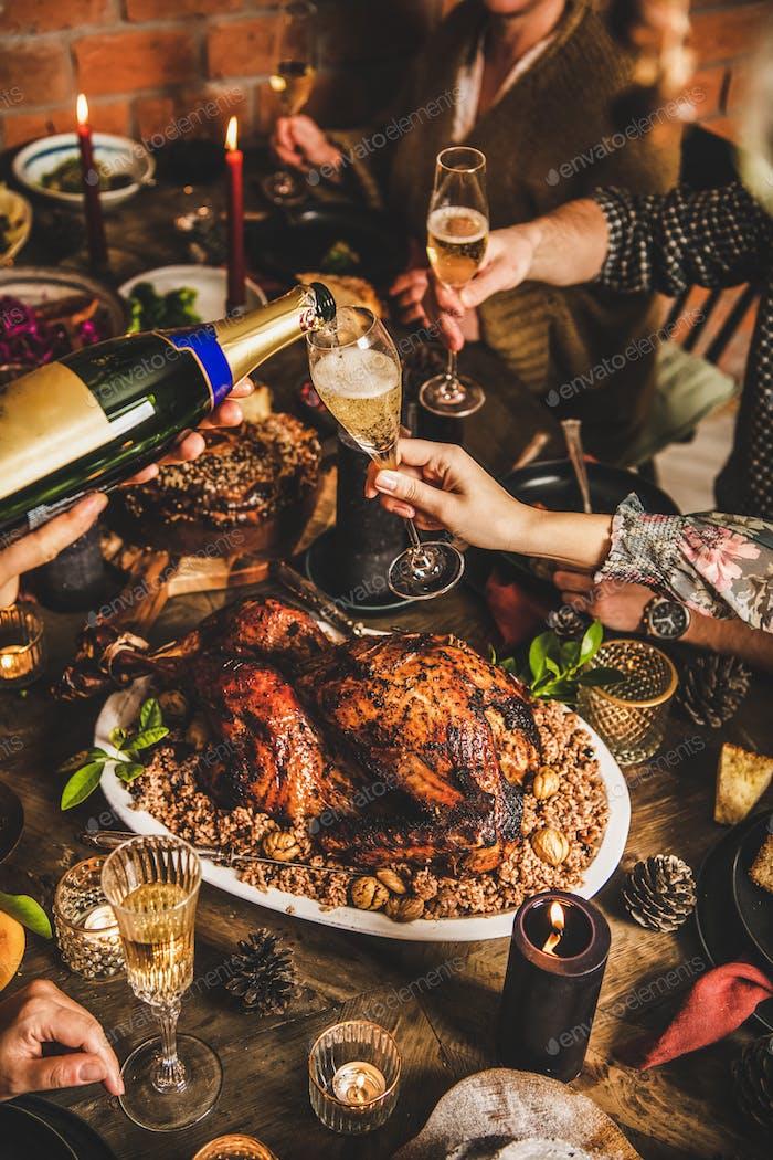 Menschen trinken Champagner über festlichen Weihnachtstisch zu Hause