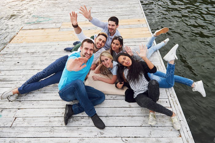 Group of beautiful young people on the pier, friends satisfaction creates emotional life