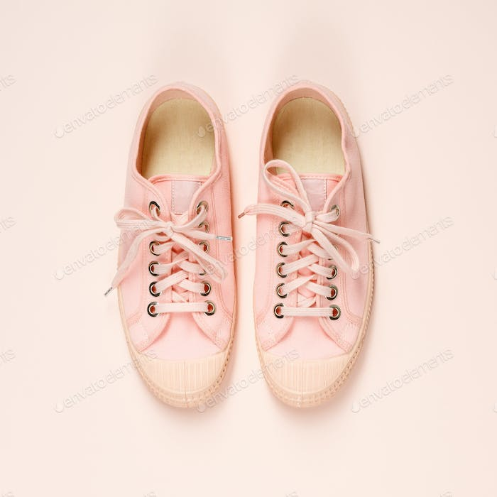 Pink canvas sneakers on pink background, close up