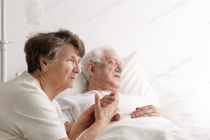Senior woman and her dying husband