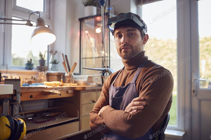 Portrait Of Male Jeweller Wearing Headband Magnifiers Working In Studio