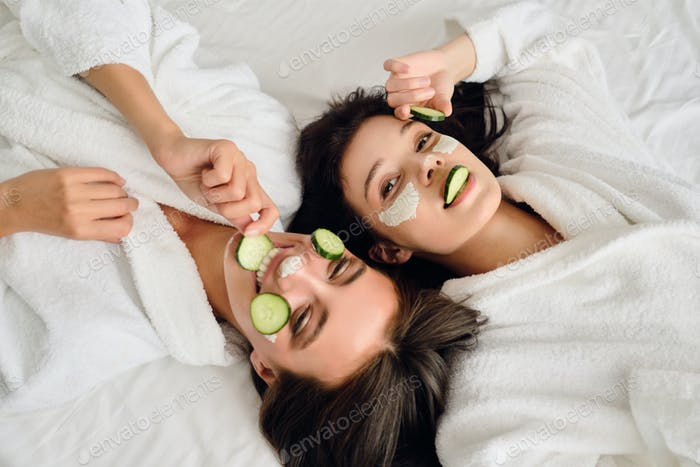 Two young women in bathrobes with cosmetic mask and slices of cucumber on faces lying in bed