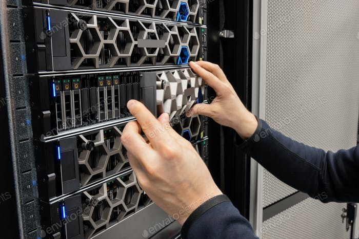 Hands Of Male Computer Engineer Monitoring Hyperconverged Servers in Datacenter