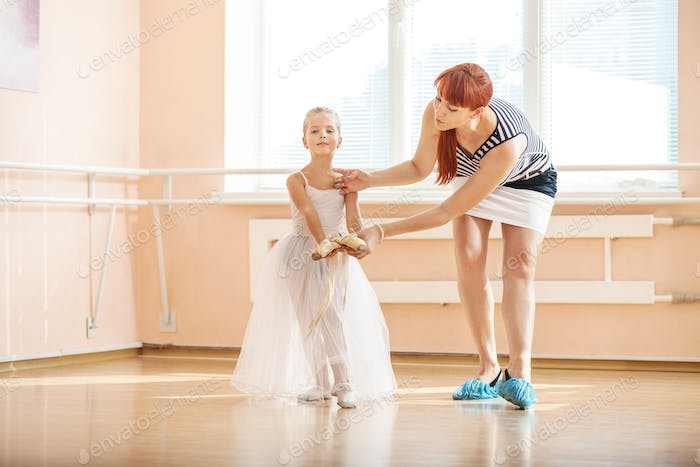 Thumbnail for Ballet teacher adjusting arm position of young ballerina dancing with pointe shoes