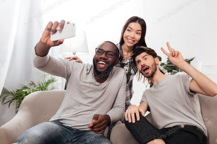 Group of smiling friends sitting on chairs at home and taking funny selfie on mobile phone together