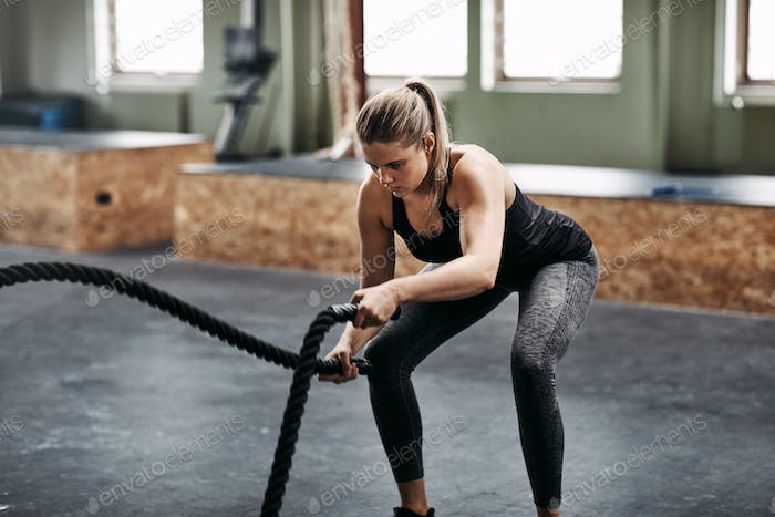 Young woman working out with ropes at the gym