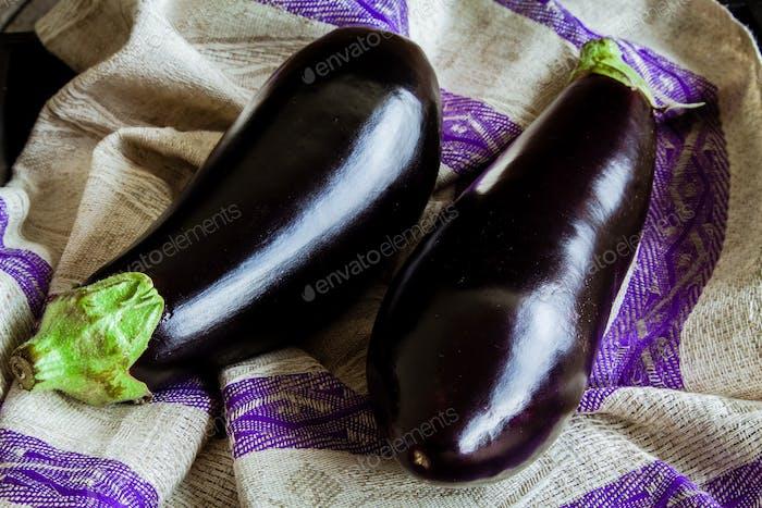 two raw organic eggplant on sackcloth