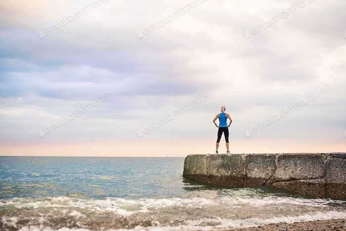 Rear view of young sporty woman standing on a pier by the ocean outside.