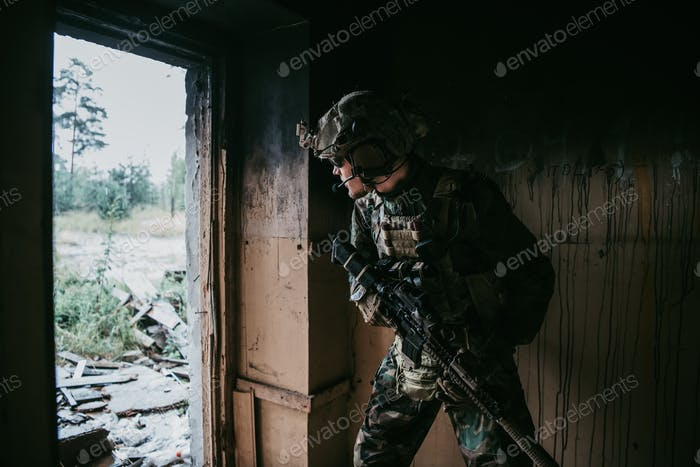 Soldier in full US MARSOC armed with assault rifle run through the abandoned building. Military