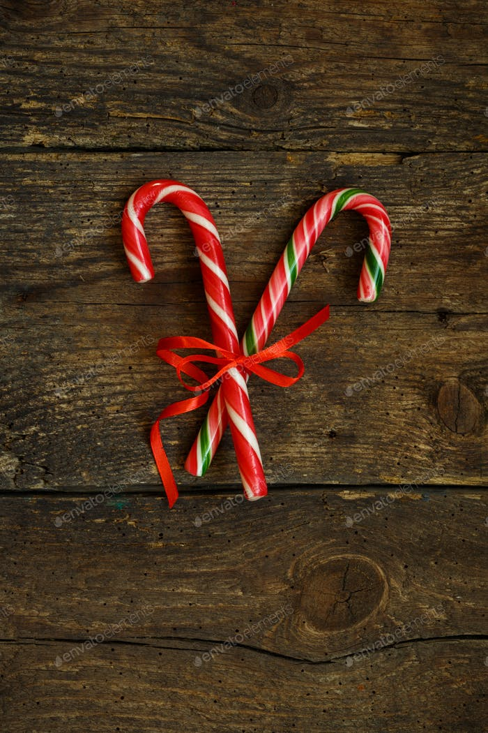 Closeup of two old fashioned candy canes on a rustic wooden back