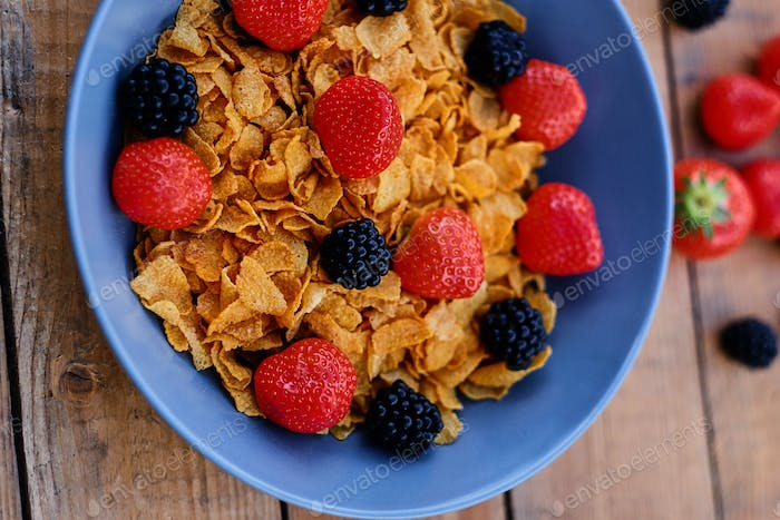 Corn flakes on a strawberry and blackberry on a plate.