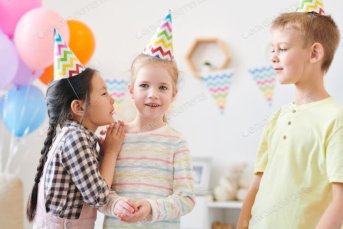 Cute little girl whispering something to one of her friends