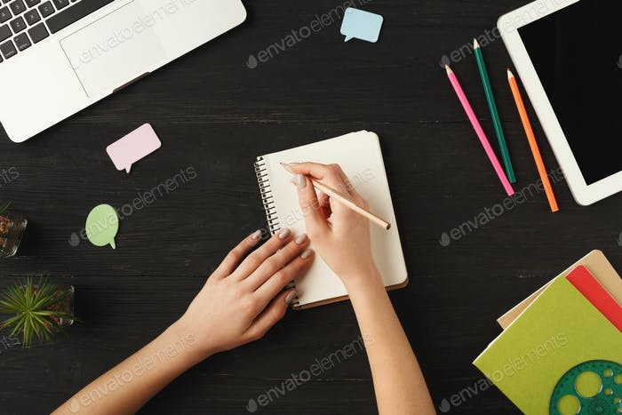 Woman's hands writing in notebook, top view