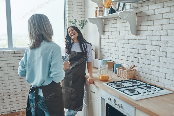 Beautiful young woman and her mother communicating while spending time at the domestic kitchen