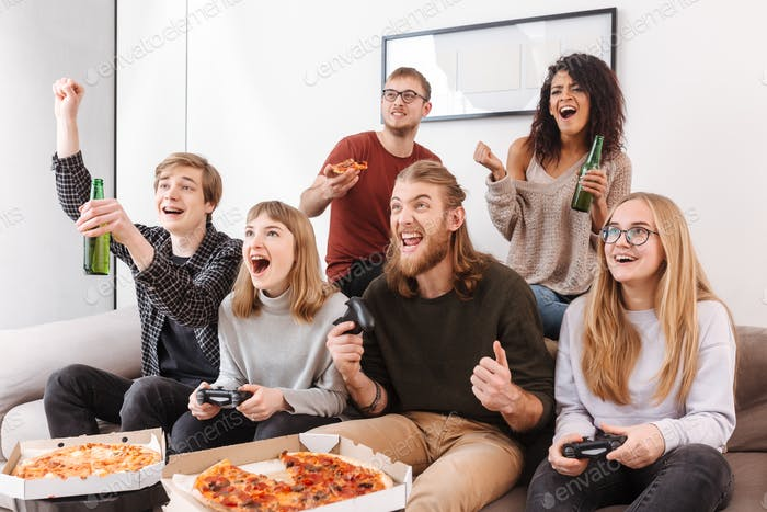 Joyful friends sitting on sofa and screaming yeah while spending time together playing video games