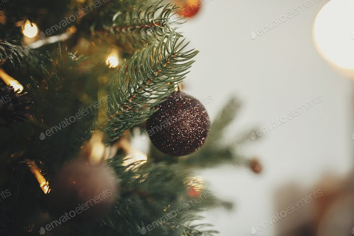 Christmas tree with ornaments, golden lights in festive room