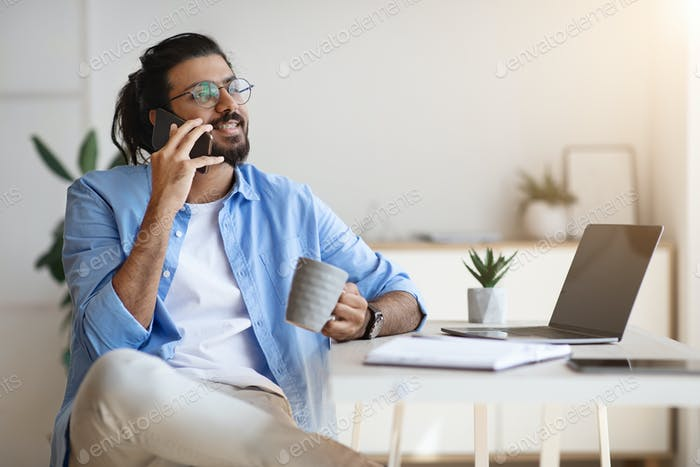 Indian Freelancer Guy Talking On Cellphone And Drinking Coffee At Home Office